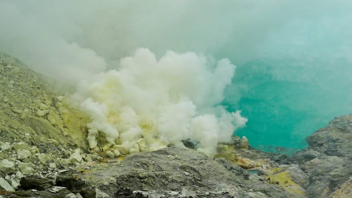 Кислотное озеро и клубы серного газа на дне кратера вулкана Иджен